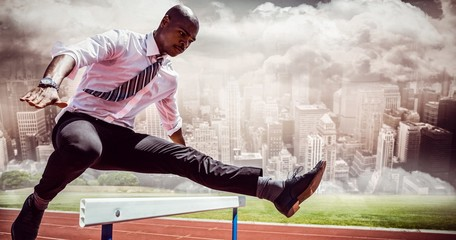 Composite image of businessman jumping a hurdle