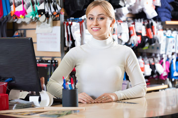Smiling blond girl cashier at the pay desk