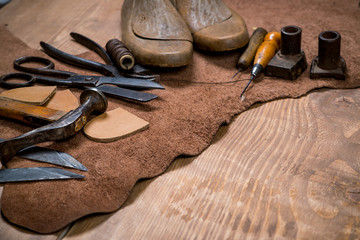 Set of leather craft tools on wooden background. Workplace for shoemaker.