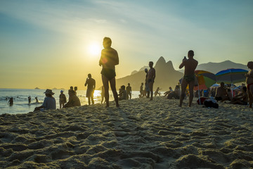 A crowd gathers on the rocks at Arpoador to watch the sun set behind the horizon at Two Brothers Mountain in Rio de Janeiro, Brazil
