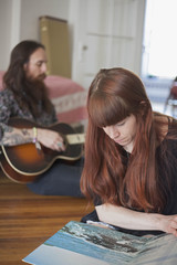 Young woman looking at a record album while her boyfriend plays
