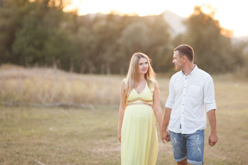 Happy and young pregnant couple walking and enjoing nature