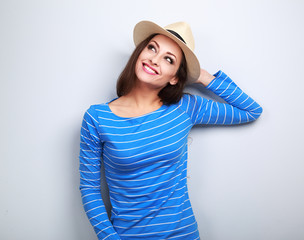Happy young woman in straw hat thinking and looking up on blue b