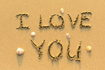I Love You - drawn by hand on a sandy golden sea beach.
