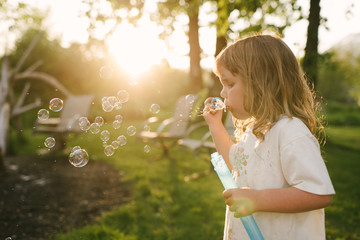 Young girl blowing bubbles with bubble wand