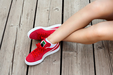 Wall Mural - Shapely woman legs in red sneakers