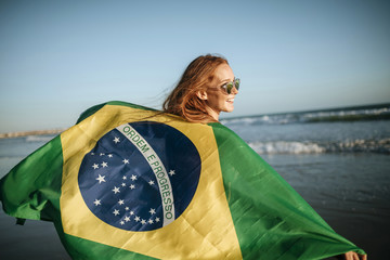 Beautiful smiling girl in sunglasses with Brazilian flag on beac
