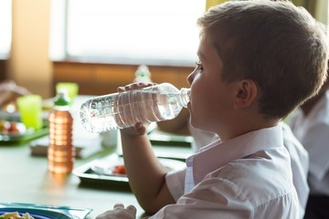 Close-up of schoolboy drinking water