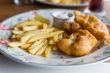 fried fish with chips on a patterned plate served with a piece of lemon and sauce.
