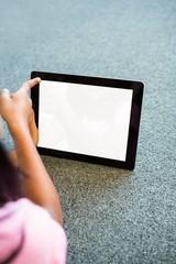 Girl using digital tablet in school library