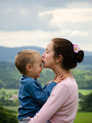 mother kissing her son outdoor