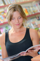 woman reading magazine inside the shop