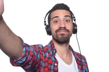 Portrait of young latin man taking selfie with headphones.