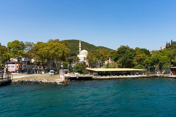 Pier with rural landscape and mosque against blue sky on the background. Turkey