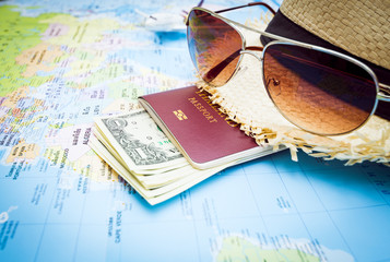 Hat, sunglasses, passport, money and aircraft on the world map