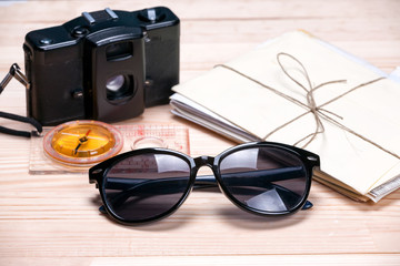 Sunglasses, compass, old film camera and a bunch of letters on l