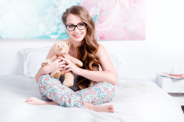 cheerful, happy, beautiful young girl in pajamas with long hair