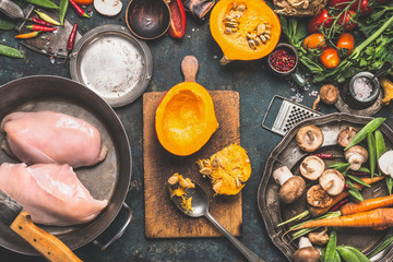 Preparation with Pumpkin , vegetables and mushrooms  ingredients with Chicken breast  in cooking pot, dark rustic background, top view Wall mural
