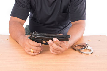 Young Man holding gun on table