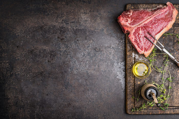 Raw T-bone Steak for grill or BBQ with meat fork and flavoring on aged cutting board and dark rustic metal background, top view, border Wall mural