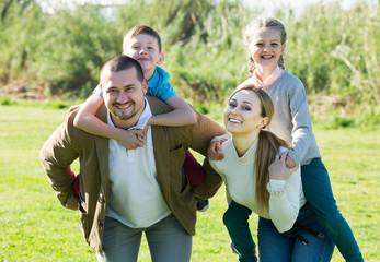 Parents holding kids on shoulders