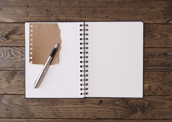An open scrapbook with pen on a wooden desk top