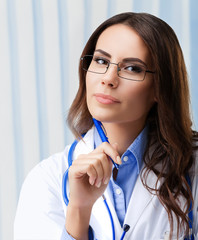Portrait of thinking female doctor in glasses