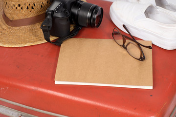 straw hat on old red suitcase