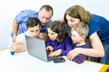 Family gathered around laptop looks at shocking content on internet, studio shot.