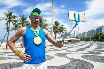 Athlete with gold medal posing for a celebratory selfie on the boardwalk at Copacabana Beach, Rio de Janeiro, Brazil