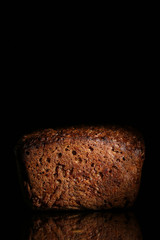 Brown bread on a black background with reflection
