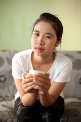 Asian woman drinking hot coffee