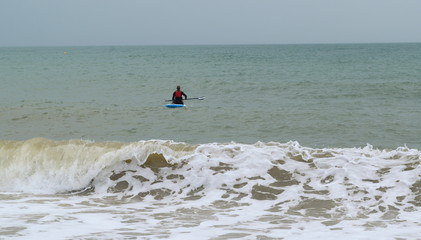 Waves and surfer in Seaton, Devon