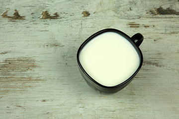 A cup of milk on old wooden vintage table