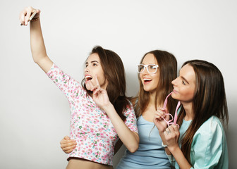 three happy teenage girls with smartphone taking selfie
