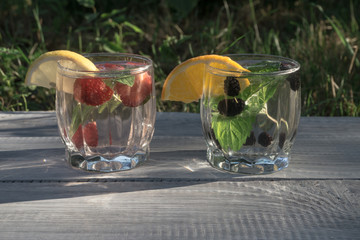 Two glasses with drink of mint and berries