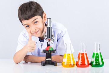 Little scientist boy with colorful flask