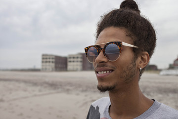 Smiling young man standing on beach