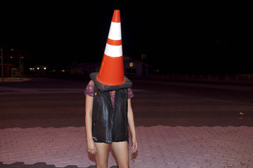 Playful young woman with a traffic cone on her head