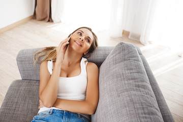 Attractive smiling young girl lying in armchair and talking on phone  at living room
