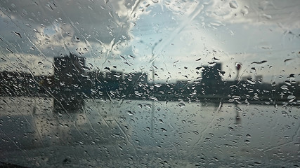 blurred silhouette of the city through wet glass