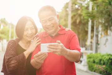 Happy senior Asian couple laughing tigether with mobile smartphone. Warm tone photo with sunlight