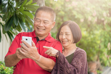 Happy senior Asian couple laughing together with mobile phone. Warm tone photo with sunlight
