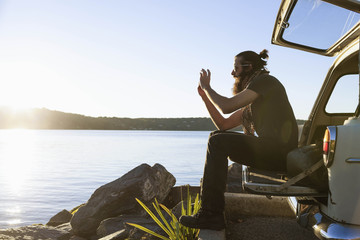 Young man taking a photograph of a scenic lake