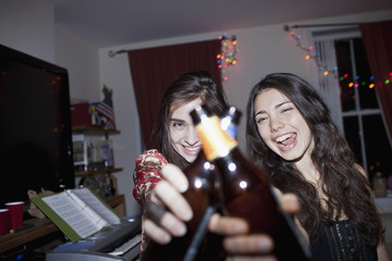 Cheerful female friends holding a beer bottle at a party