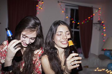 Cheerful female friends drinking at the party