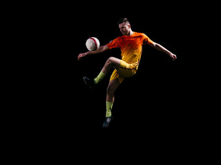Professional soccer player in red kicking ball in jump