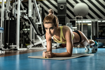 young fitness woman execute exercise plank