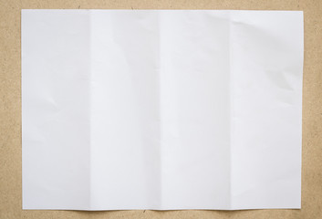 Full page of White paper folded and wrinkled on wood brown background with shadow