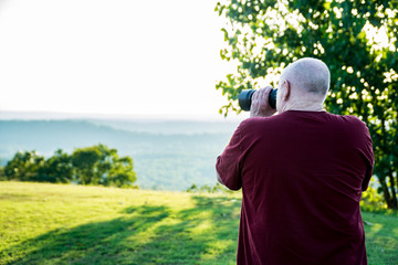 A Man Photographing a Wildlife at the Edge of the Woods